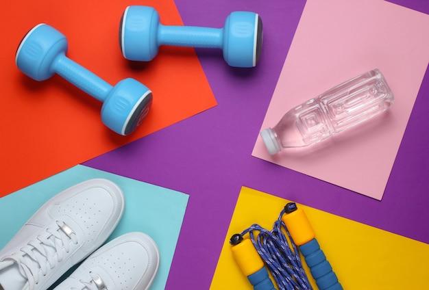 フラットレイスタイルのスポーツコンセプト。ダンベル、スニーカー、縄跳び、ボトル入り飲料水。色付きの背景にスポーツ用品。