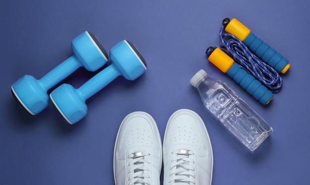 フラットレイスタイルのスポーツコンセプト。ダンベル、スニーカー、縄跳び、ボトル入り飲料水。紫のスポーツ用品