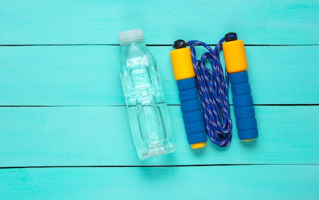 Flat lay style sport concept. jump rope, bottle of water. sports equipment on blue wooden background.