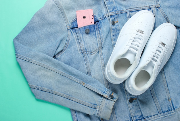 Flat lay style white hipster sneakers with a denim jacket, audio cassette