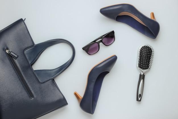 Flat lay style аксессуары женской одежды на белом фоне сумка кожаная обувь на высоком каблуке солнцезащитные очки гребень