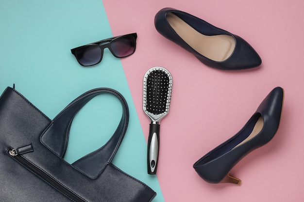 Flat lay style womens clothing accessories on pink blue background bag leather high heel shoes sunglasses comb