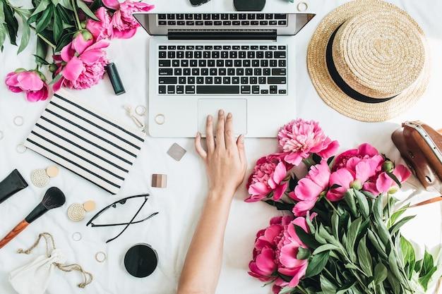 Плоский офисный стол в стиле модной одежды с ноутбуком, розовыми цветами пиона, косметикой, аксессуарами. женщина, работающая на компьютере. вид сверху