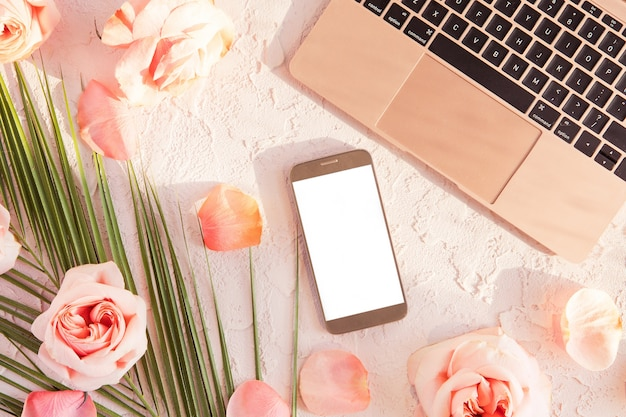 Flat lay of stylish composition with laptop, mobile phone. tropical palm leaf, pink rose flowers, on pastel with shadows and sun light