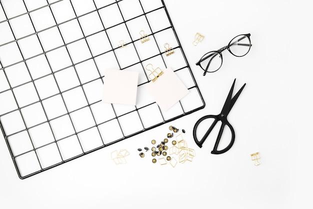 Плоские лежал стильный набор очков, ножниц, скрепок, заметок на белом фоне