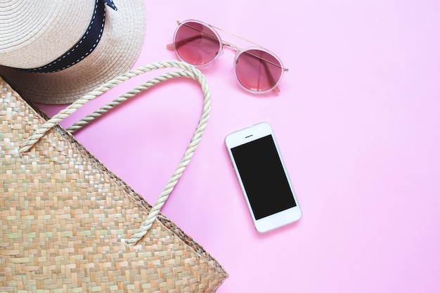 Flat lay of summer accessories with mobile device on pink colour background.