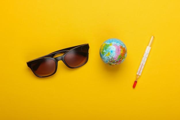 フラットレイ夏の背景。ビーチでの休暇。温度計付きの地球儀、黄色の背景にサングラス。地球温暖化。上面図