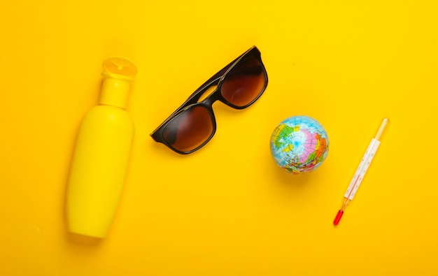 フラットレイ夏の背景。ビーチでの休暇。黄色の背景に温度計、サングラス、日焼け止めボトル付きの地球儀。地球温暖化。上面図