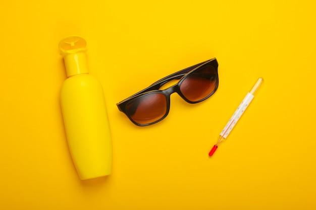 フラットレイ夏の背景。ビーチでの休暇。黄色の背景に温度計、サングラス、日焼け止めボトル。上面図