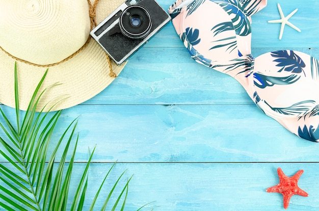 Flat lay summer background with palm leafs, starfishes and bikini