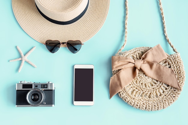 Flat lay of summer bag, sunglasses, beach hat, camera and smartphone on green