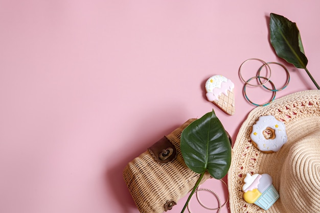 Flat lay summer composition with female accessories on pink background copy space.