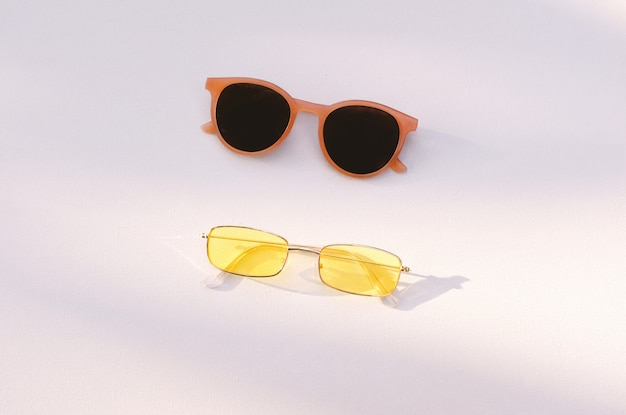 Flat lay summer fashion accessories concept of two sunglasses on white background with sunlight, vacation and summertime background