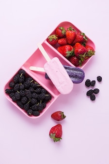 Flat lay summer ice cream with strawberries and blackberries