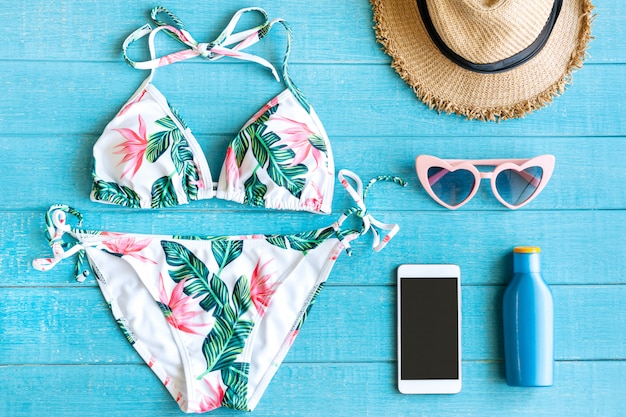 Flat lay of summer items with colorful bikini; smartphone; sunglasses; straw hat; suncream and smartphone on blue wooden table; copy space; top view. tropical summer concept.