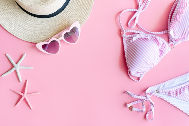 Flat lay of summer items with stripe pattern pink and white color bikini, coral in starfish shape