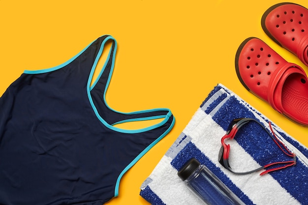 Flat lay summer pool accessories on a yellow background colorful beach wear
