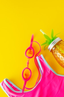 Flat lay summer yellow background with pink swimsuit and beach objects.