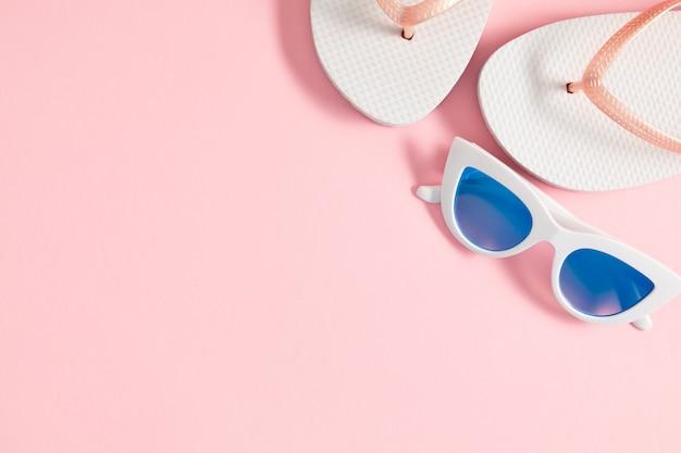 Плоские солнцезащитные очки и пляжные аксессуары на розовом фоне