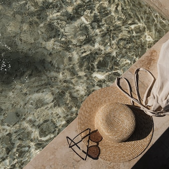 Flat lay of sunglasses and straw hat on marble swimming pool side with clear blue water with waves sunlight shadow reflections
