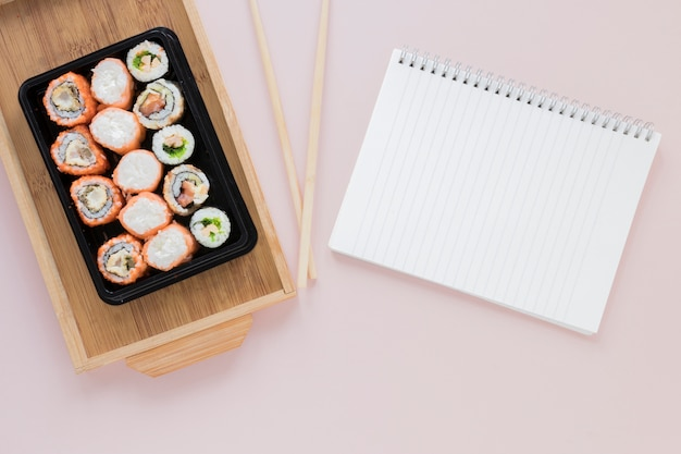 Flat lay sushi composition with notepad template
