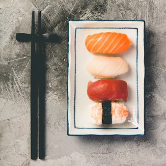 Flat-lay of sushi on a grey stone background, close up