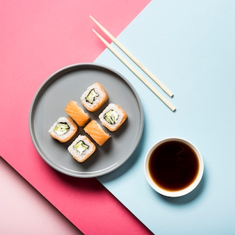 Flat lay sushi plate with chopsticks and soy sauce