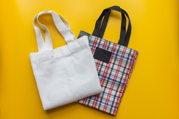Flat lay of sustainable products cloth bag on yellow