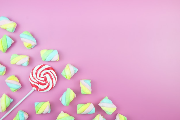 Flat lay sweet candy lollipop marshmallow colourful pink background