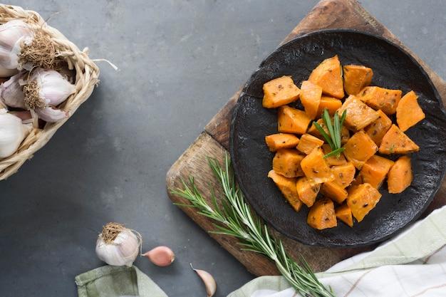Плоские лежал сладкий картофель на черной тарелке
