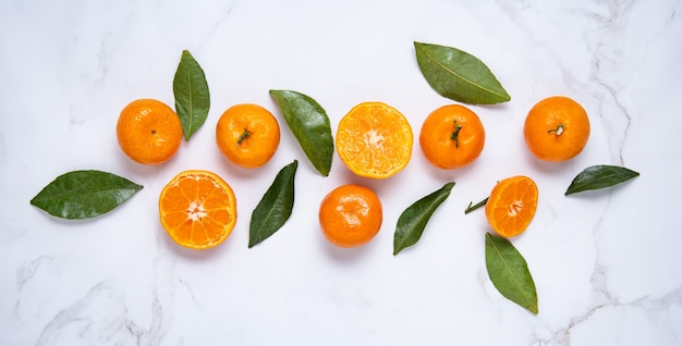 Flat lay sweet tangerines and green leaves on a white marble