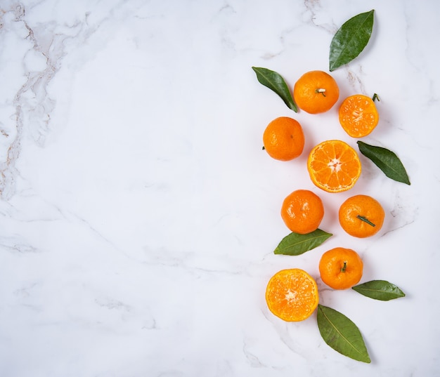 Flat lay sweet tangerines and green leaves