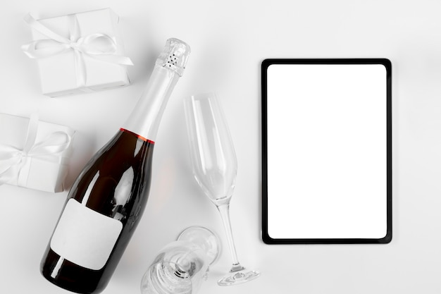 Flat lay tablet next to champagne bottle