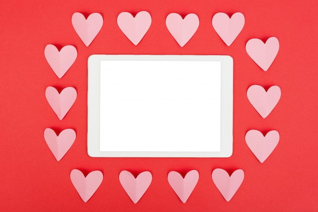 Flat lay of tablet computer with blank screen on red background with paper hearts