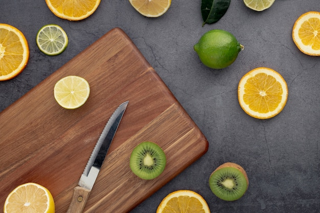 Flat lay of tangerines and kiwi slices with chopping board and knife
