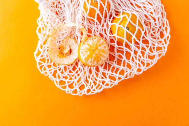 Flat lay tangerines in a mesh shopping bag, zero waste concept