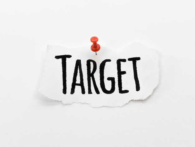 Flat lay of target written on piece of paper with pin
