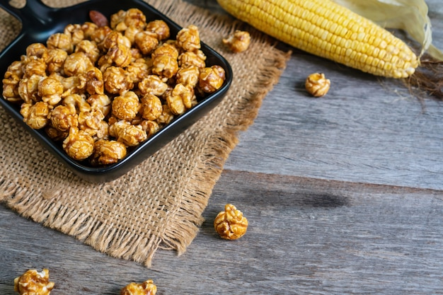 Flat lay of tasty caramel popcorn in black ceramic pan plate with corn and sack table cloths on wooden table, close up.