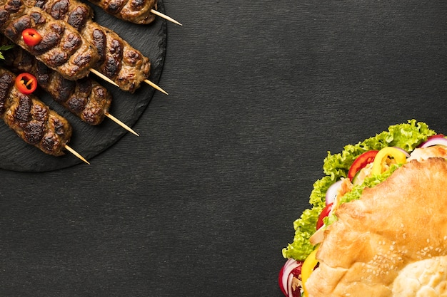 Flat lay of tasty kebab on slate with copy space