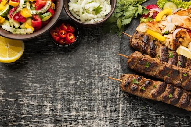 Lay piatto di gustosi kebab su ardesia con altri piatti e verdure