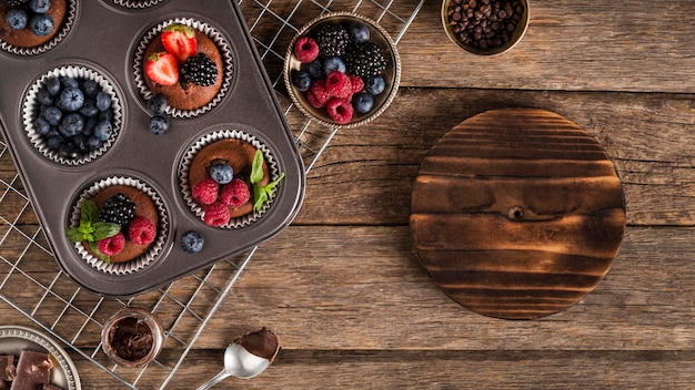 Flat lay tasty muffin with forest fruit in baking tray