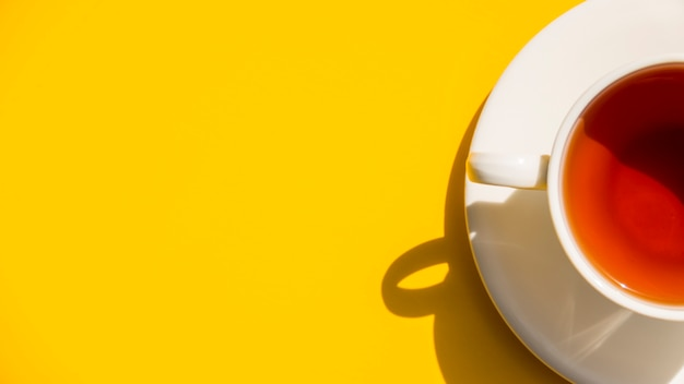Flat lay tea cup on yellow background