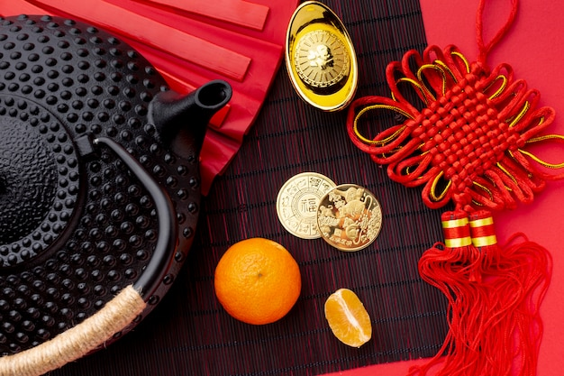 Flat lay of teapot and golden coins chinese new year