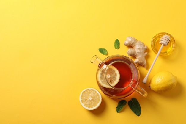 Flat lay. teapot, lemon, ginger, mint, honey and dipper on yellow, copy space