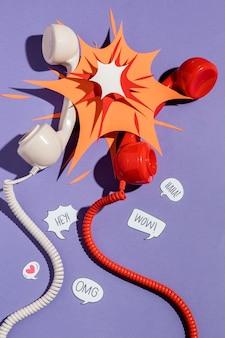 Disposizione piatta di ricevitori telefonici con forma di carta e bolle di chat