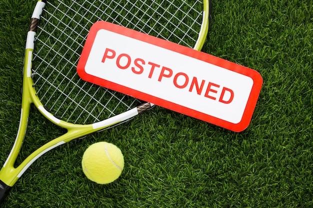 Flat lay tennis elements arrangement with postponed sign