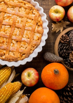 Flat lay of thanksgiving apple pie with corn and pine cones