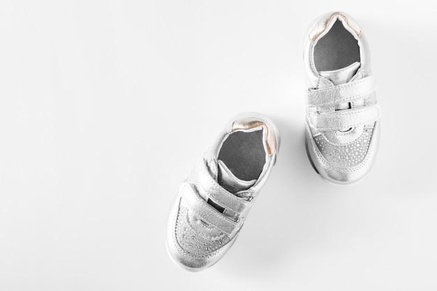 平らに置きます。白い背景に分離された銀の子供用スポーツシューズ