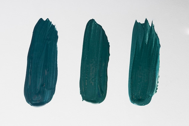 Flat lay of three creative blue paint brush strokes on surface