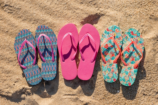 Flat lay of three pairs of flip flops